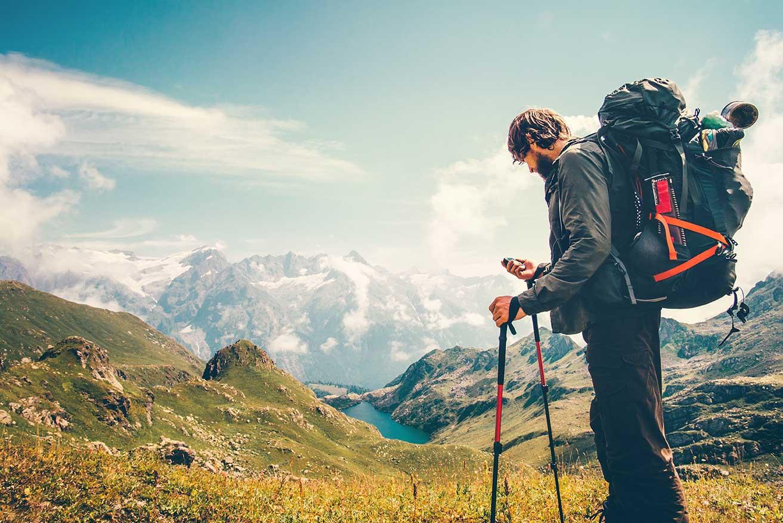 Hombre con ropa de montaña, mochila con equipamiento de montaña y un palo sosteniendo su teléfono móvil en la cima de una montaña.