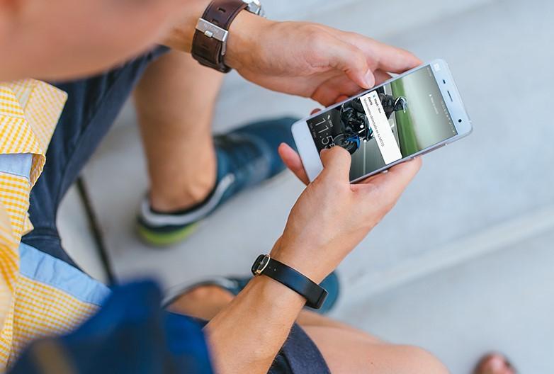 Hombre jóven sosteniendo un teéfono móvil Xiaomi con la pantalla encendida y una notificación de Mapit indicando que su moto se ha movido