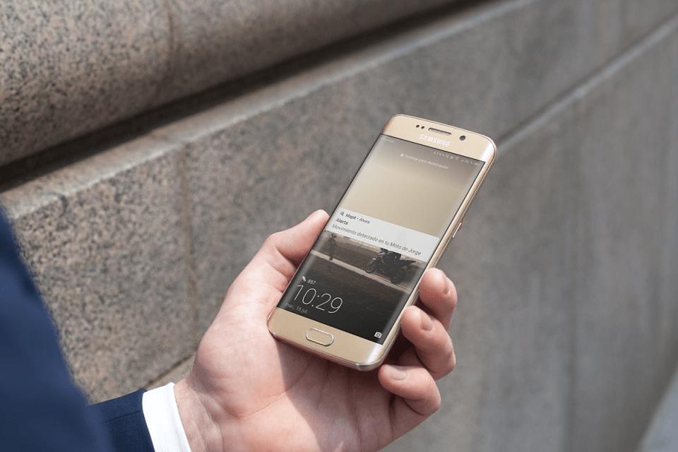 Mano de un hombre con traje sosteniendo un teléfono móvil Samsung galaxy S6 con la pantalla encendida y una notificación de Mapit indicando que su moto se ha movido