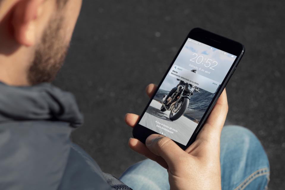 Hombre jóven sosteniendo un teléfono móvil iPhone con la pantalla encendida y una notificación de Mapit indicando que su moto se ha movido